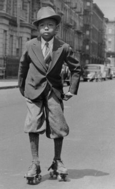 Smartly dressed boy on roller skates in Harlem, NY, 1920s/1930s.