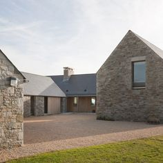 Seaside house in Ireland by Tierney Haines Architects where three sandstone wings protect an inner courtyard from coastal winds..