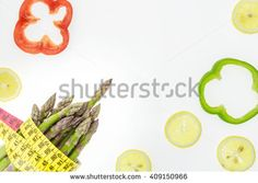 Asparagus spears with measuring tape, lemon slices and pepper rings, on white background with copy-space