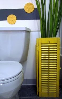 2 shutters, spray painted and nailed together. Cute idea and can be used to conceal plunger and cleaning brush
