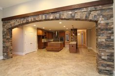 View from the great room: a stone-wrapped archway with stained wood accent above leads the way into the two island kitchen. Stone Interior, Arch Interior, Interior Ideas, Interior Design, Stone Archway, Stone Columns, Living Room Partition Design, Room Partition Designs, Ikea Kitchen Design