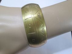 Tribal brass bangle bracelet from India.  Unpolished, vintage measures approx.  Great etched hieroglyphic style design, mountains, sun.  Brass related