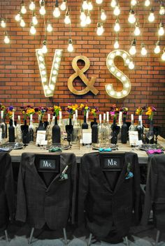Theme: HIPSTER WEDDING  Red Events Design Studio Floret Paper Panache Cake Sensations  Ed Williams Mens Wear    Hipster wedding decor, hanging filament lightbulbs, lit up monogram, suit jackets over grooms chairs, wine bottles for flowers and candles centre piece
