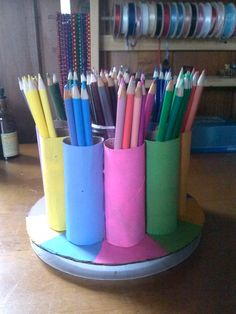 Painted toilet paper rolls glued to a piece of cardboard make a great colored pencil holder.