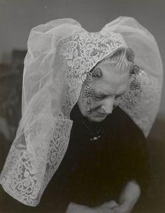 Vrouw in Noord-Bevelandse streekdracht. 1956 Ze draagt over een zwarte ondermuts de lange sluiermuts met een 16 centimeter brede strook kloskant. Aan de krullen van het oorijzer hangen 'catrieljebellen'. Tussen de krullen twee 'torenspelden', waarmee de muts aan het oorijzer is gespeld. Het haar is in 'draaitjes' gelegd. #NoordBeveland #Zeeland