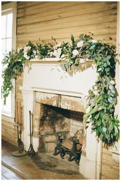 Fireplace mantle with white rose and eucalyptus garland by Stems & Styles, image by White Rabbit Studios.
