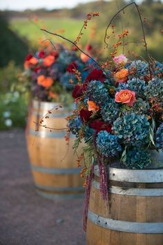 Blue hydrangea and branches atop wine barrels are the perfect winery wedding flower arrangement. Petalworks.