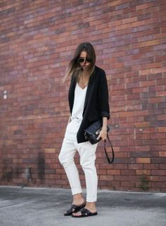 White blouse with black long sweater and white casual plan jeans and black leather hand bag and black pumps