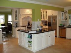 a kitchen island built around a pillar with a microwave on the