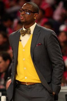 The bright yellow cardigan makes this tradition suit stand out. Photo GQ