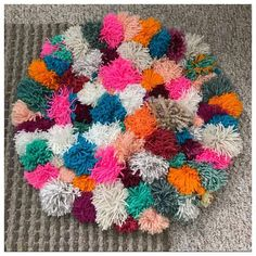 Absolutely adorable multi color pom pom rug. Handmade one by one pom pm tied onto a 2 round rug. Add a pop of color to your room and a whole lot of cuteness