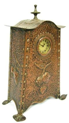 ENGLISH ARTS & CRAFTS BEATEN COPPER MANTEL CLOCK, CIRCA 1910,  the later dial enclosed by tapering case with riveted brackets to the angles and a repoussé decorated vine motif to the centre, 36cm high