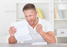Man cheering in jubilation as he reads a letter ...  announcement, approval, approved, books, businessman, casual, caucasian, celebration, confirmation, desk, document, employee, envelope, exam, excited, excitement, fist, furniture, gesture, good, handsome, happy, holding, home, joy, leadership, letter, mail, male, man, mature, message, news, notice, notification, page, paper, reading, receiving, results, shelves, success, surprise, surprised, t-shirt, table, validation