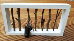 DIY Schlüsselbrett mit im Wald gesammelten kleinen Ästen in einem weiß gestrichenen Holzrahmen. Der Rahmen ist mit Nägeln zusammen gebaut.