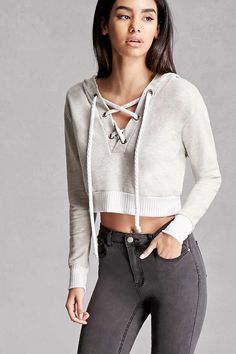 A heathered knit top featuring a hood, lace-up front with grommets, ribbed trim, French terry cloth lining, a cropped silhouette, and long sleeves. This is an independent brand and not a Forever 21 branded item.