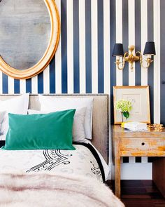Blue and white striped wallpaper in bedroom with round, gold mirror, emerald pillow on bed, and salvaged wood bedside table