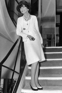 Standing at her favorite observation spot, Rue Cambon's spiral staircase, Chanel sports the costume jewelry and two-tone shoes the brand still produces today.