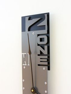 This modern clock uses material cutouts to depict numbers in a variety of ways (standard, written, and roman numeral). The purpose of the missing material is to allow the color(s) behind the clock to show through creating a more integrated wall feature. It also features background pieces which can be colored differently than the foreground for more contrast.  Outnumbered VII Modern Wall Clock Granite w/ Back by All15Designs