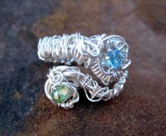 "Hand-Formed Adjustable Ring    Materials: Swiss Blue Topaz Set in Sterling Silver and Swarovski Crystal ""Entwined"" with Silver Plated Wire."