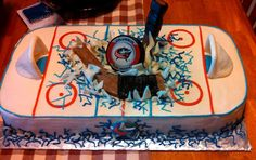 """Blue Jackets Hockey Rink cake. Hockey puck and """"broken stick"""" bursting through the ice rink! Everything but the puck is all edible candy clay and buttercream!  https://www.facebook.com/angelas.cakes2011"""