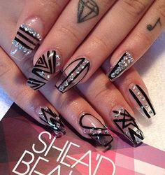 Artsy looking stick on nails in black tribal polish designs. The silver embellishments on top help make the nail art look very interesting.