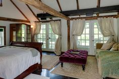 Renee Zellweger has my taste. French doors and exposed beams add rustic glamour to the master bedroom.