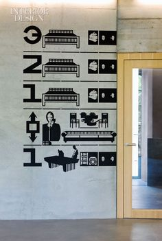 Painted on the concrete lobby wall at the Jugendherberge Basel, graphics indicate the functions on each level. Photo by Filippo Bamberghi/Photo Foyer.
