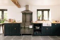 A simple run of dark blue deVOL Shaker cupboards with a Smeg range cooker