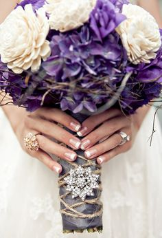 bouquet with purple hydrangea, purple lisianthis, cream balsa wood flowers, and accented with an angel vine collar. The stems were banded with pewter satin ribbon, with a twine handle treatment,   and finished with a little bling... a sunburst rhinestone brooch. via Heavenly Blooms: Rustic Wood With a Modern Metallic Edge - Wedding Inspiration