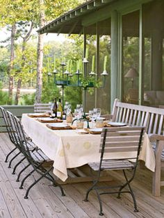 Large candelabras dress up the casual wooden deck furniture, and a park bench increases seating at the table.