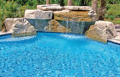 Swimming pool with large rock waterfall
