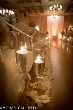 Tall candle holders with floating LED candles light and line the aisle.