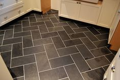 16″ black gauged slate tiles cut in half and layout out to create a herringbone pattern.