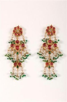 A pair of traditional gold ear pendants set with diamonds, rubies and emeralds, suspended are pearls and green glass beads.  Provenance: India, Rajasthan 19th century.