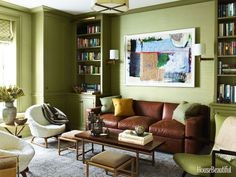 """The library, with Farrow & Ball's Olive paint and Phillip Jeffries's Vinyl Thai Silk wall-covering, represents """"a warmer zone.""""  Tommi Parzinger coffee table with pullout stools and Kurt Østervig chairs for Rolschau MØbler date from the 1950s. Sofa by A. Rudin. Rug by Stark."""