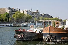 Ships and embankment on the river of the Seine, Paris, in a sunny spring day.