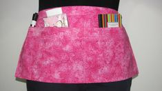 This handmade pink waist apron would be perfect for teachers, vendors, crafters and servers alike! This very feminine apron features three reinforced pockets, a butterfly and flower print on pink fabric and a lovely rose button. Description: Pink fabric with a flower and