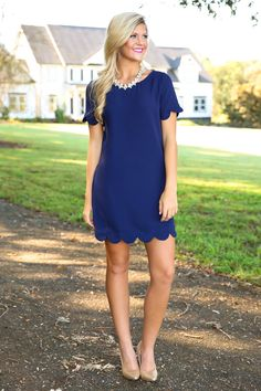 Slip into this Navy Scallop Dress and let it show you how life can be Sweeter Than Fiction! Turn the page on bland style and take on this tempting to touch and wear number that will always leave a sweet taste in your mouth and on your frame!! Shift dress features a crew neckline, a keyhole on the back with a gold button loop closure, and scalloped sleeves and hemline. Model is wearing a small.  • 100% Polyester  • Hand Wash Cold • Unlined • Imported