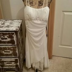 """Ruby Rox"" Evening Dress Off-white/ cream evening/ dance dress. Sz S. Beaded empire waist. Roughed on both sides. 100% polyester, hand wash. There are a few loose strings in beaded area (see last picture). There is a mark on the inside of the bust (see 3rd picture).  Underarm to under is 13.5"" . Narrowest part is waist is 12"".  hem is a high low. Dress is 24"" from empire waist to highest point of the front hem. Ruby Rox Dresses High Low"