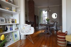 living room, via The Shimmer #exposedbrick #woodfloors #modern #greycouch #nickel #tripodlamp #grayrug #yellow #gray #exposedbrick #structube #modernbookcase #eiffelchair #rust #ledapeony #dove