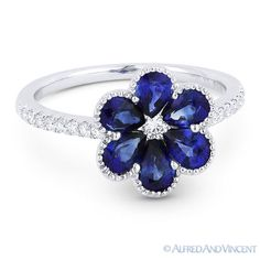 The featured ring is cast in 18k white gold and showcases a centerpiece flower design adorned with a round cut diamond centerstone, pear-shaped blue sapphire petals, and round cut diamond accents set halfway along the band.