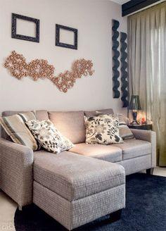 Objetos práticos se tornam itens decorativos na parede da sala de TV: perto da cortina, estão posicionados dois revisteiros metálicos de design sinuoso e, logo acima do sofá, quatro sousplats artesanais, costurados um ao outro pela moradora. Projeto de Elvira Monteiro.