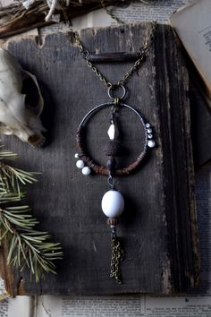A handcrafted necklace created with wire various salvaged beads and  salvaged leather