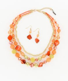 Layered chains are accented with  mixed orange beads and fabulous gold-tone mesh balls. Set includes double drop bead earrings. -Necklace: 17 - 21 inches -Earrings: 2 inches