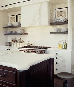 White kitchen with open shelving, white subway tile, contrasting island, and Calacatta Gold marble custom range hood. Mind = Blown.