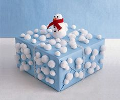 Glue pom-poms in various sizes to a blue wrapped package. Stack and glue large pom-poms together to make a snowman