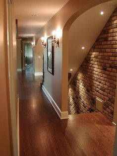 Basement entrance. Love the lighting and brick wall and how inviting it is with no door!