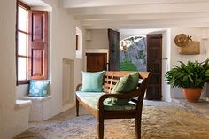 The main entrance of a rural house in mallorca. Large doors in wood, stone floors and walls painted in white. chicandrustic.blogspot.com.es