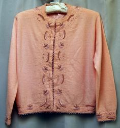 Vintage 1960's Pink or Peach Beaded Cardigan Sweater. This is a soft pink or peach cardigan beaded with pink beads and pink shiny pearls. It is beaded all around the bottom hem, neckline, up the front, and at the wrists. The beadwork has a triangular or looped beaded edge that extends off the fabric at the edges.  This has seven metal hook and eye closures up the front, and is lined in the bodice. I am not sure of the fabric, but I think it is a wool or angora blend.