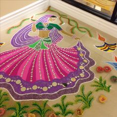 Dancing Radha for Diwali celebrations Hand painted colorful sand on the floor , free drawing and decorated with jewels and glitter.